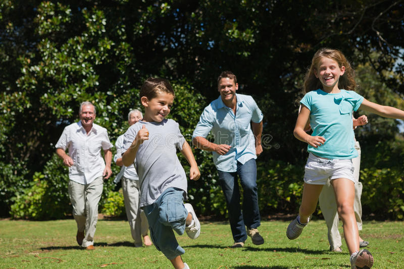 赛跑往照相机的愉快的多一代家庭 免版税库存图片