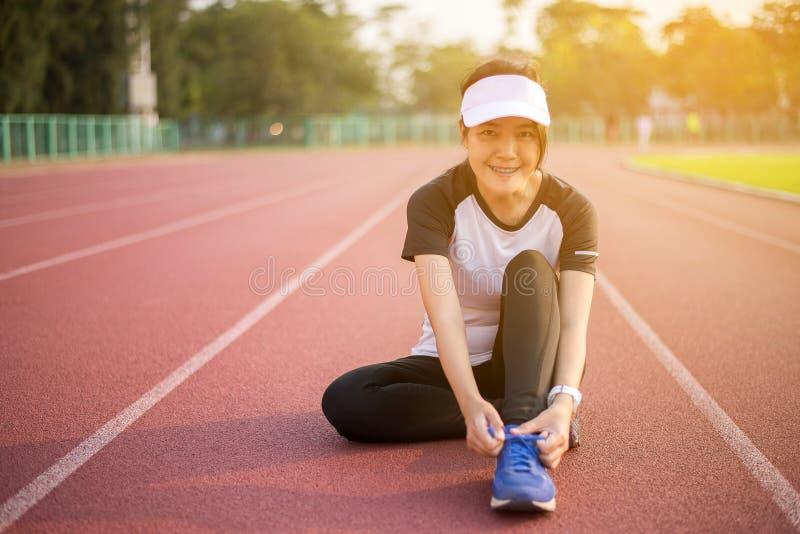 赛跑者亚洲妇女栓在跑鞋的鞋带,妇女运动室外为跑步做准备或的奔跑 库存图片