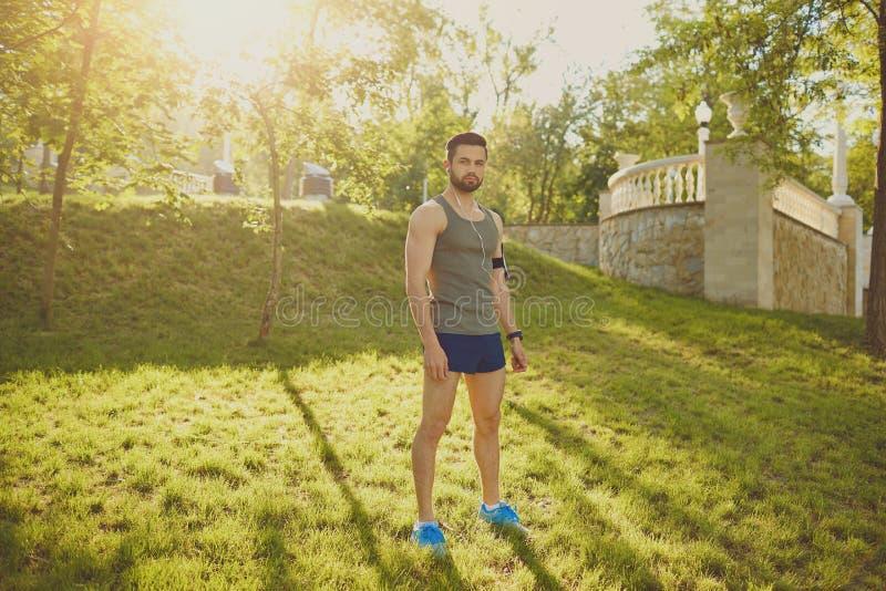 赛跑者人在公园站立在日落 库存图片