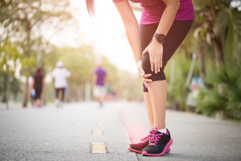赛跑者体育膝伤 妇女在膝盖痛苦中,当跑在公园时解决 背景弄脏了关心概念表面健康防护屏蔽的药片 免版税库存图片