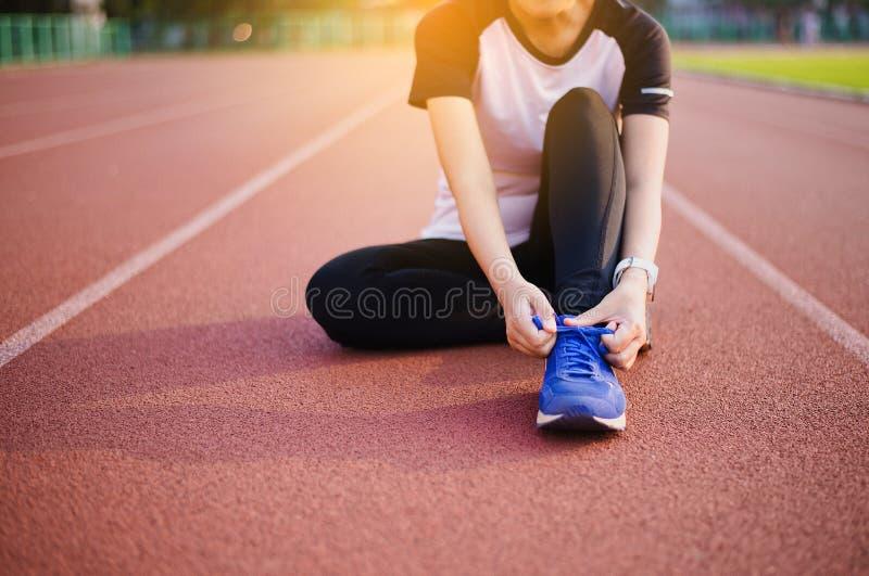 赛跑者妇女栓在跑鞋、女子室外运动员为跑步做准备或的奔跑的鞋带 库存照片