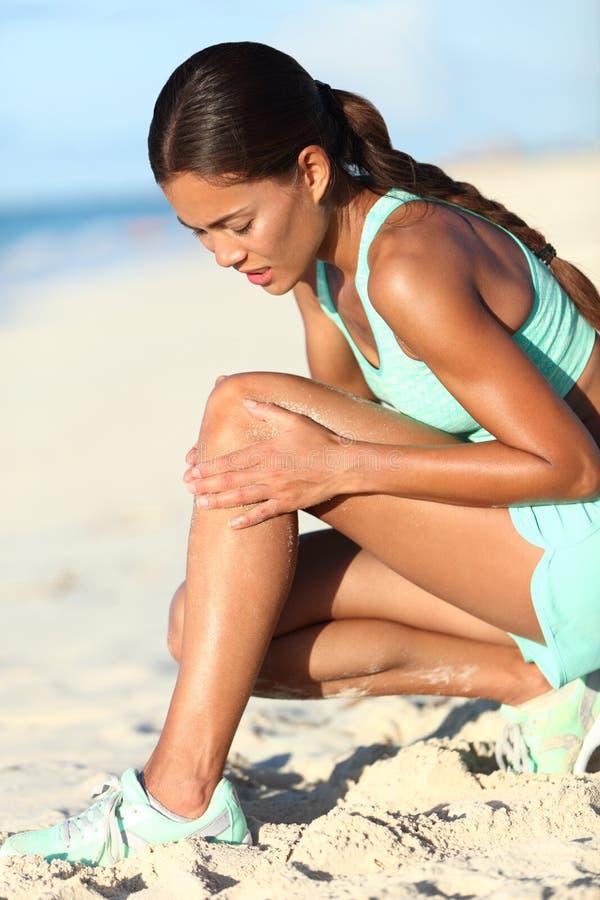 赛跑者腿伤-有损害的膝盖痛苦亚裔连续妇女 免版税库存图片