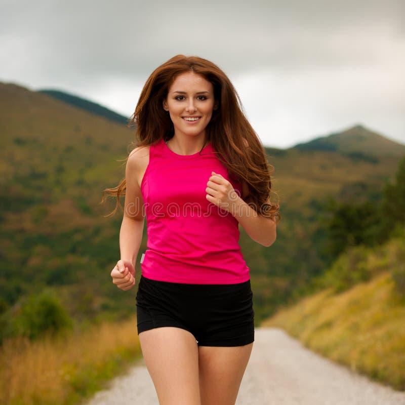 赛跑者-在森林公路的妇女runns -室外锻炼 免版税库存照片