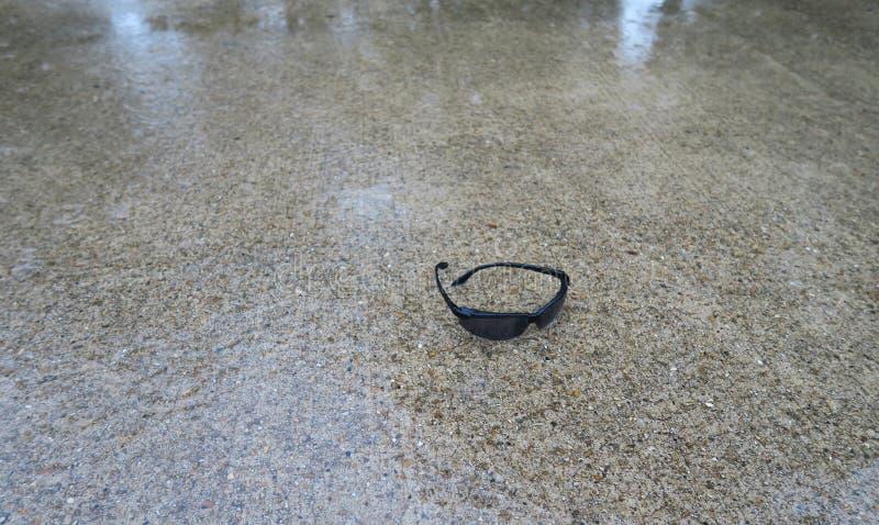 赛跑者` s太阳镜忘记了,当跑在雨中时 库存照片