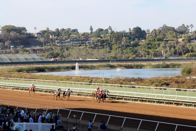 赛马在轨道、人前景的,水、喷泉和树在背景中 免版税库存图片
