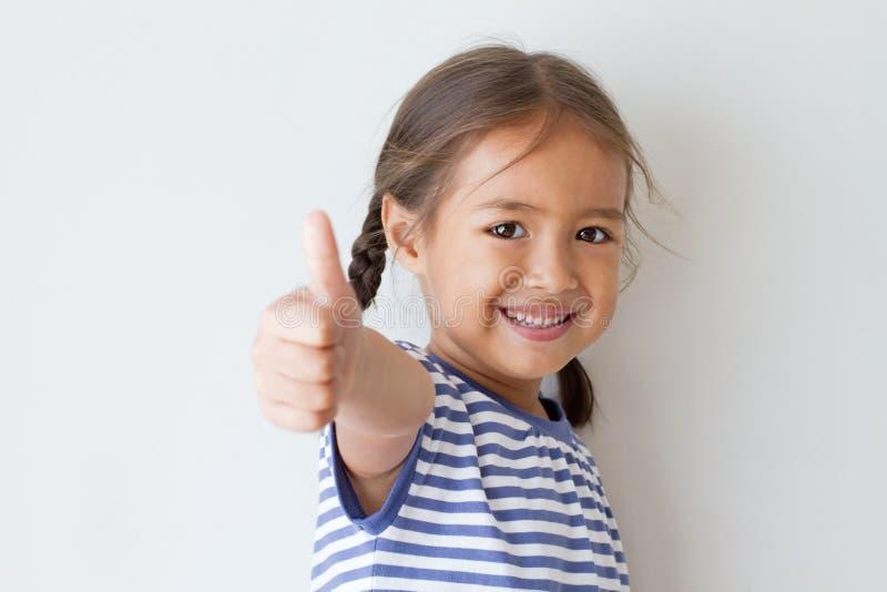 给赞许手标志的女孩 免版税库存图片