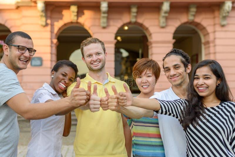给赞许标志的微笑的青年人 免版税库存图片