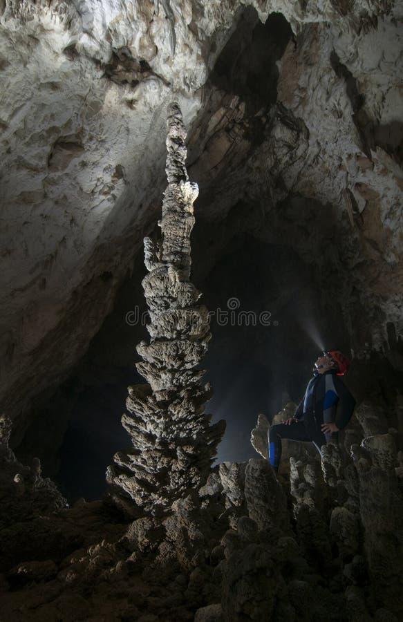 洞赞赏的大石笋的洞穴学者 免版税图库摄影