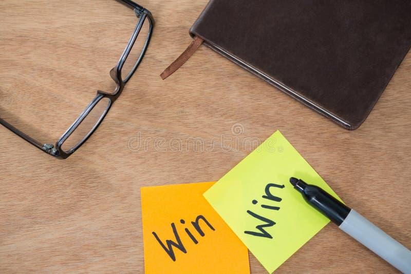 赢取写在与标志、眼镜和日志的稠粘的笔记 免版税图库摄影