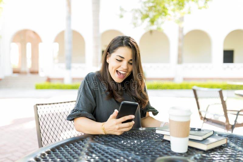 赢取的抽奖惊奇的妇女读书新闻在智能手机的 免版税库存照片