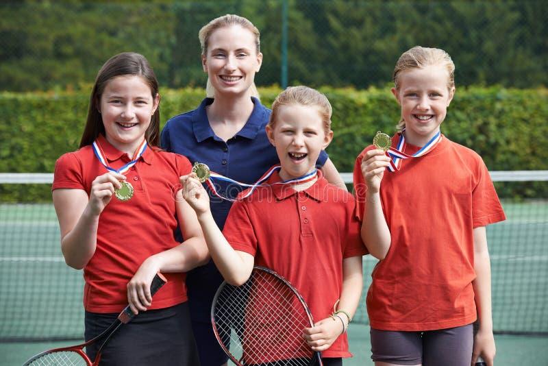 赢得与奖牌的女性学校网球队画象  免版税库存图片