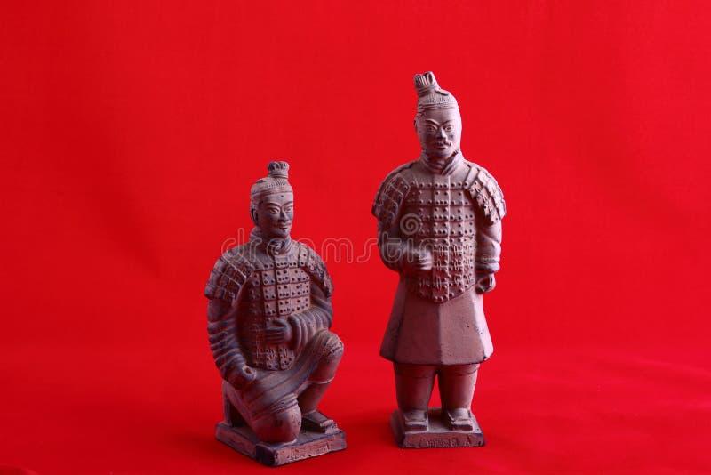 赤土陶器在红色背景的战士雕象 免版税库存照片