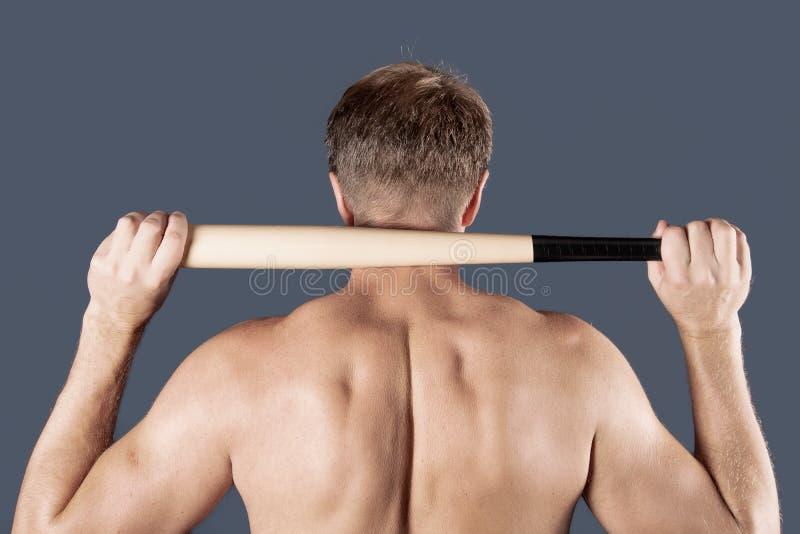 赤裸上身的人在他的肩膀拿着在蓝色背景的一个棒球棒 库存照片