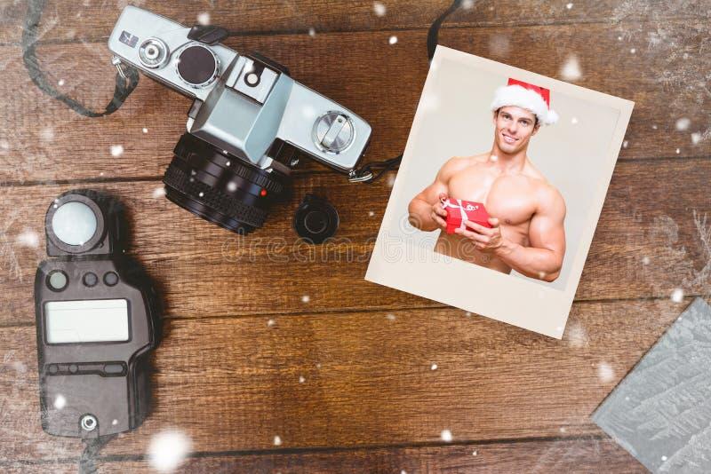 赤裸上身的强壮男子的人的综合图象拿着礼物的圣诞老人帽子的 免版税库存图片