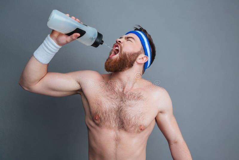 赤裸上身的有胡子的年轻人运动员站立的和饮用水 免版税库存图片