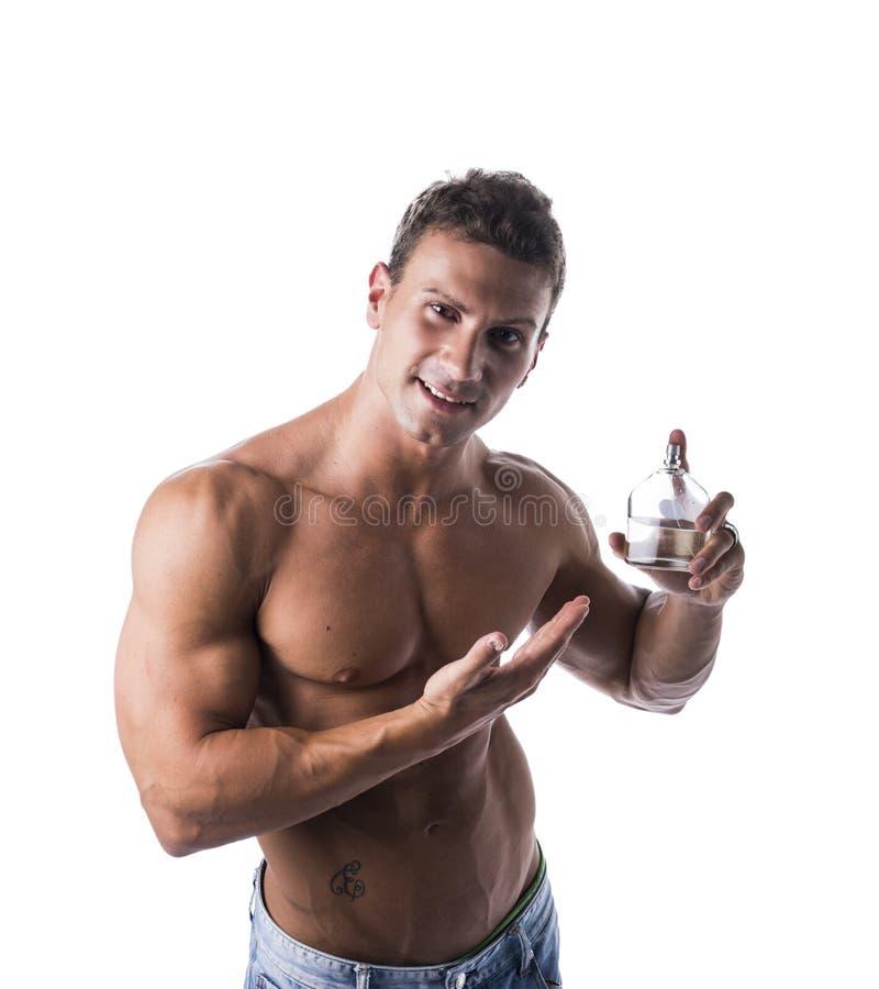 赤裸上身的肌肉男性式样显示的科隆香水瓶 免版税库存图片