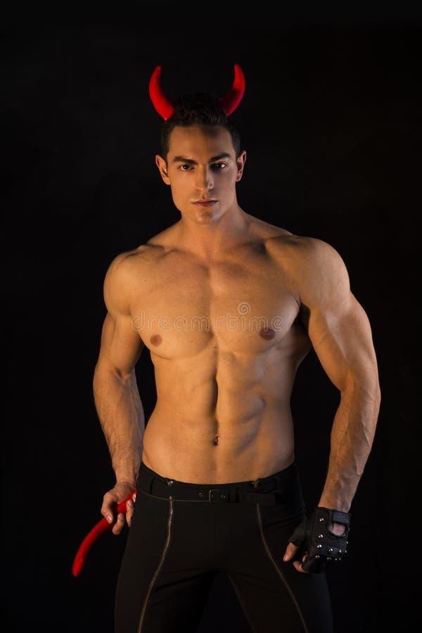 赤裸上身的肌肉男性爱好健美者穿戴了与恶魔服装 免版税库存照片