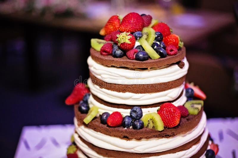 赤裸婚礼巧克力蛋糕冠上用莓果 库存图片
