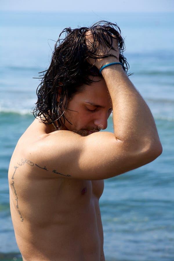 赤裸男性设计在哀伤的水中 库存照片