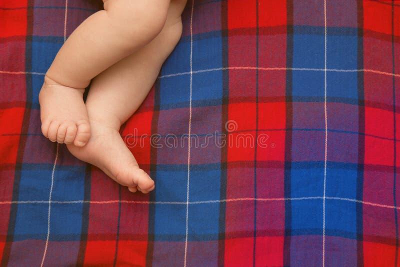赤裸婴孩腿新出生在格子呢 方格的背景 的treadled 免版税库存照片
