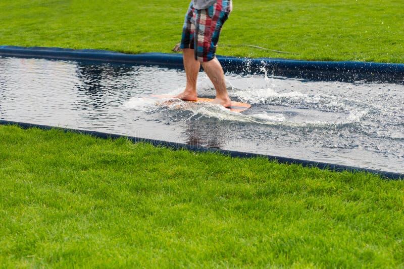 赤足冲浪者横跨水池在船上飞溅 免版税库存照片