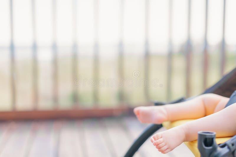赤足微小的婴孩在婴儿推车 免版税库存图片