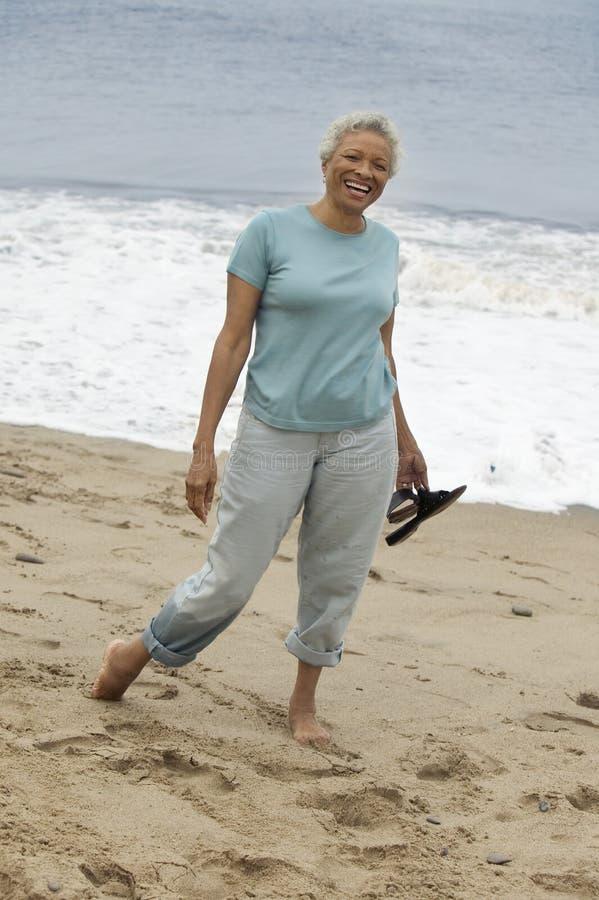 赤足站立在海滩(画象)的资深妇女 免版税库存图片
