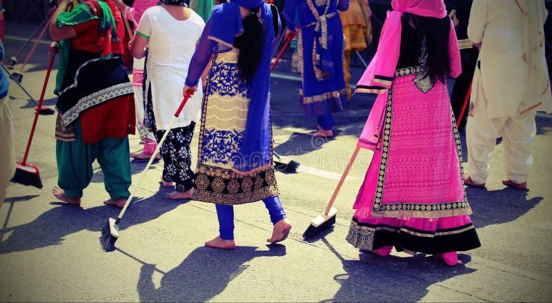 赤足许多锡克教徒妇女,当清除路在一个锡克教徒的节日期间时 库存照片
