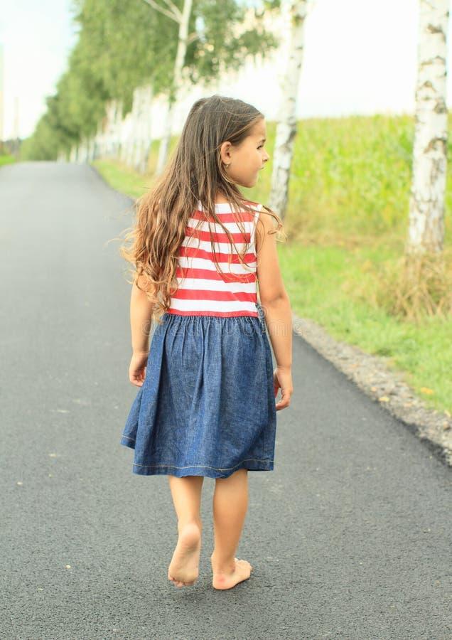 赤足走在沥青街道上的小女孩 库存图片