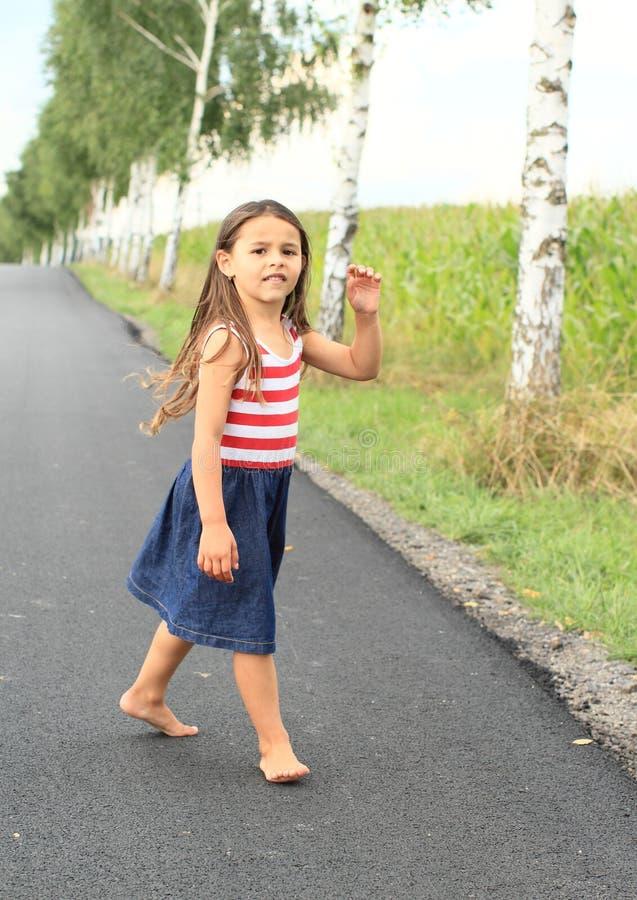 赤足走在沥青街道上的小女孩 免版税库存照片