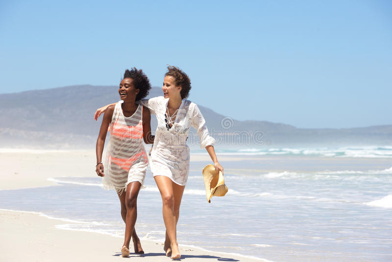 赤足走在海滩的两个少妇 免版税库存照片