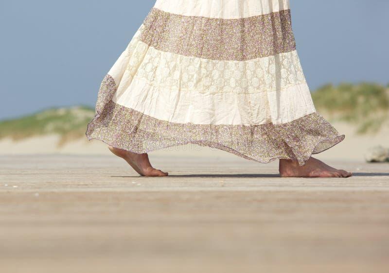 赤足走在海滩的女性 库存图片
