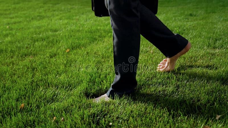 赤足走在绿草的男性,放松在工作以后,梦想关于假日 免版税库存照片