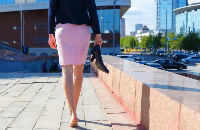 赤足走妇女保险开关的画象户外 女孩、少年、学生或者企业夫人衣服的沿城市街道去 免版税库存图片