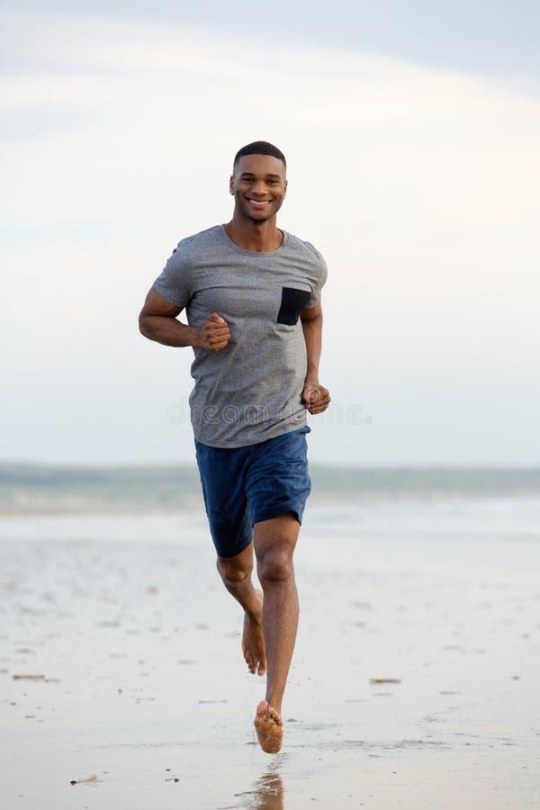 赤足跑微笑的年轻的人 免版税库存图片