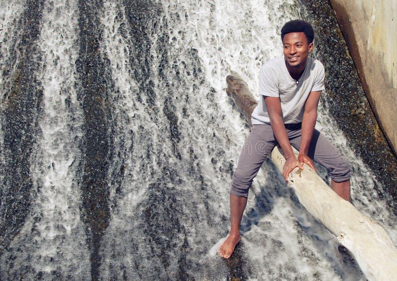 赤足年轻人在河坐树干瀑布 免版税库存照片