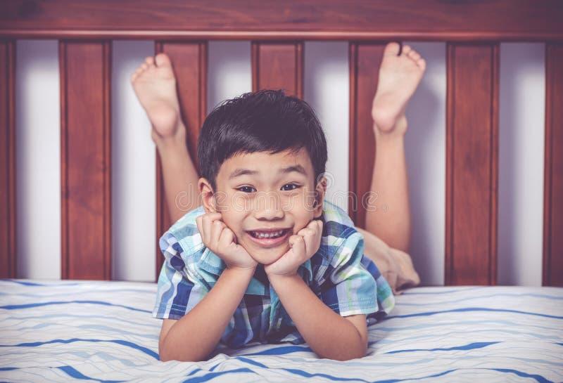 赤足说谎在床上的英俊的男孩在卧室 愉快的儿童smili 免版税图库摄影