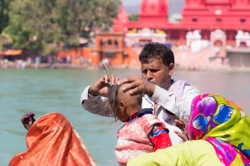 赫尔德瓦尔,印度- 2017年3月20日:供以人员刮年轻印度献身者启蒙的头发在恒河在赫尔德瓦尔,印度 免版税库存照片