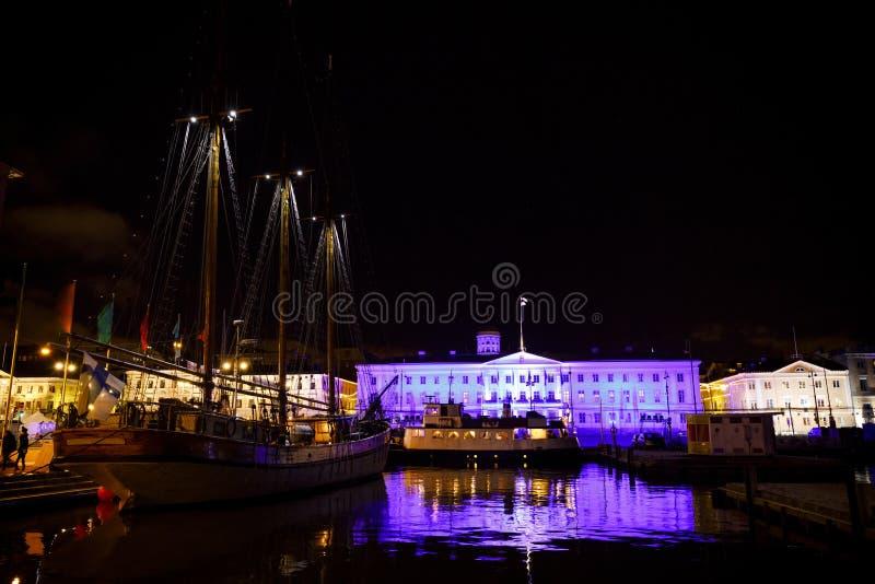 赫尔辛基市政厅和帆船在晚上 库存图片