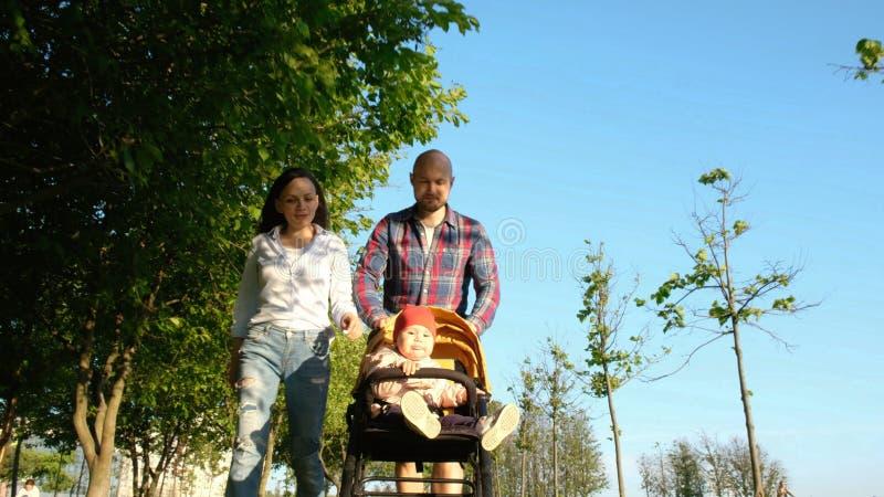 走与一个孩子的父母在公园 愉快的家庭:妈妈和爸爸滚动了摇篮车的孩子本质上在日落 免版税库存图片