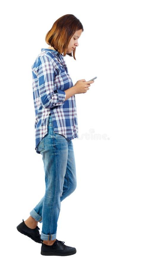 走与一个手机的妇女的侧视图 库存图片