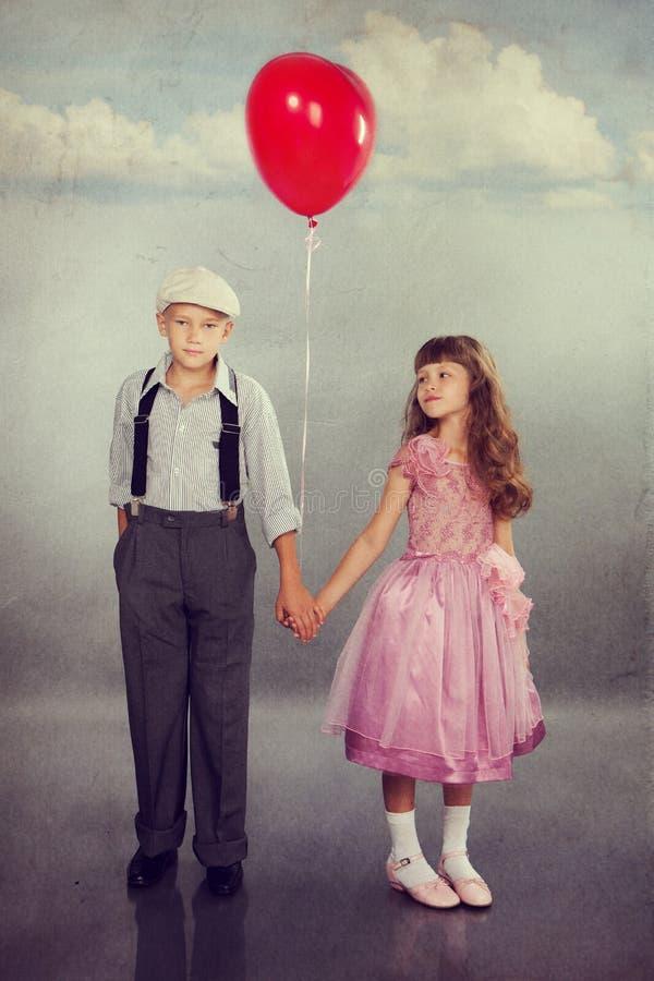 走与一个红色气球的逗人喜爱的孩子 库存图片