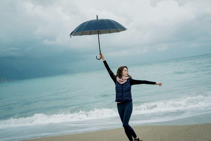 走与一把伞的少妇在前面海在冬天或a 免版税库存图片