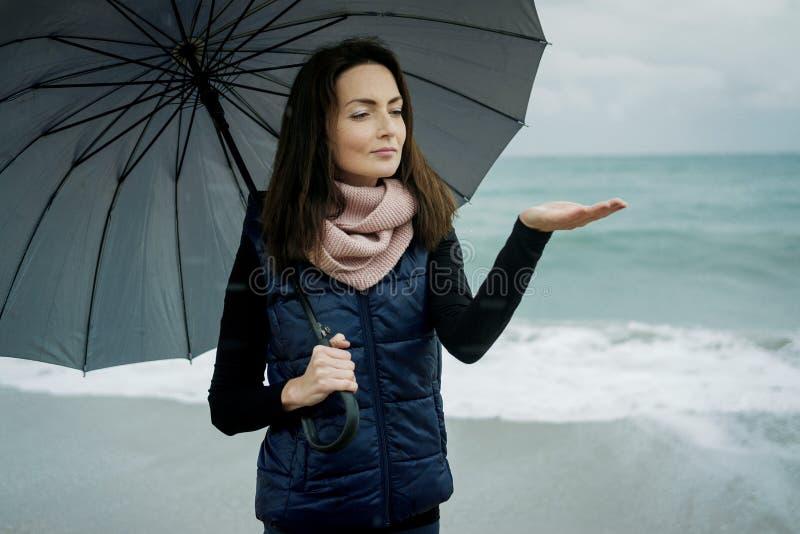 走与一把伞的少妇在前面海在冬天或a 免版税库存照片