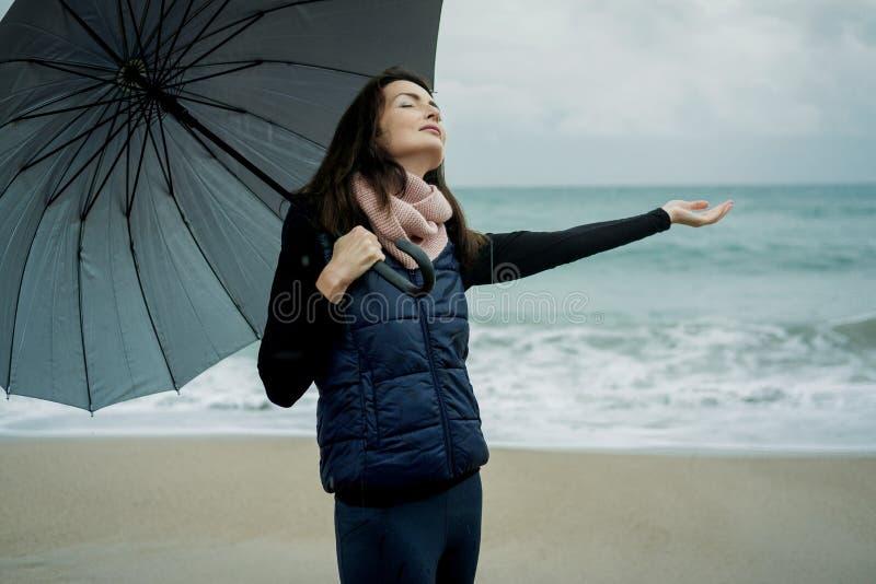 走与一把伞的少妇在前面海在冬天或a 图库摄影