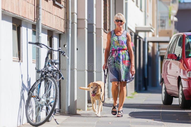 走与一条狗的妇女在城市 免版税图库摄影