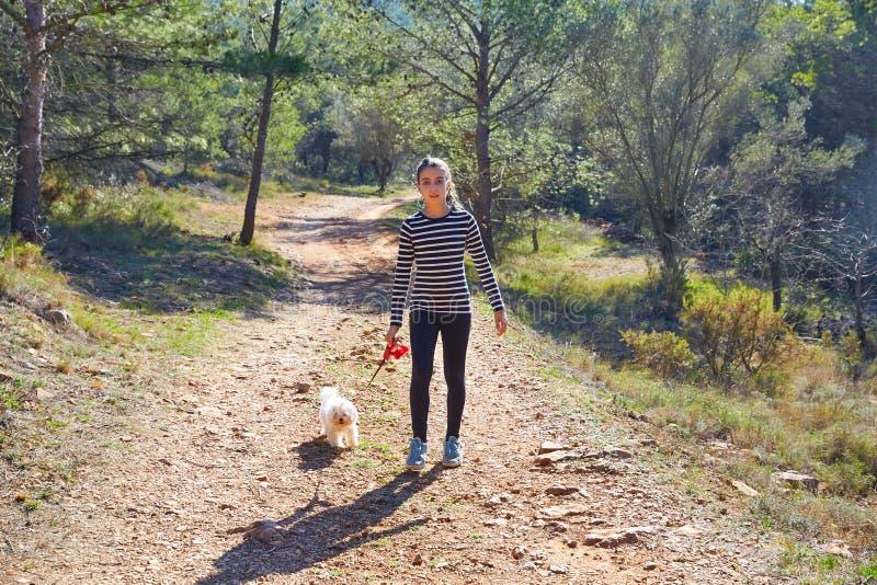 走与一条白色狗的青少年的女孩在森林里 免版税库存图片