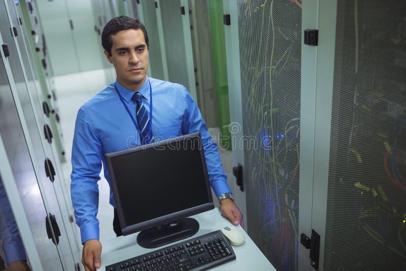 走与个人计算机的技术员在走廊 免版税库存图片