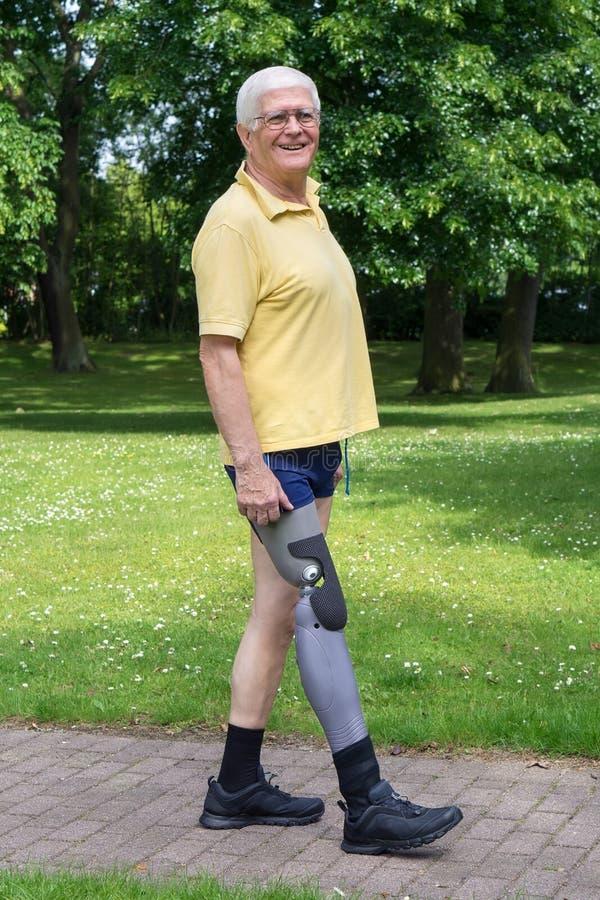 走与义肢腿的愉快的更老的人 免版税图库摄影