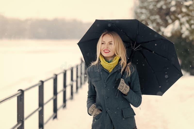 走与伞的女孩在冬日 有长的金发的妇女在白色雪风景 免版税库存照片